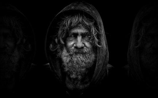 Obdachloser Mann auf dunklem Hintergrund